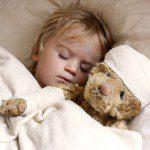 boy and teddybear in bed, with teddy bandaged