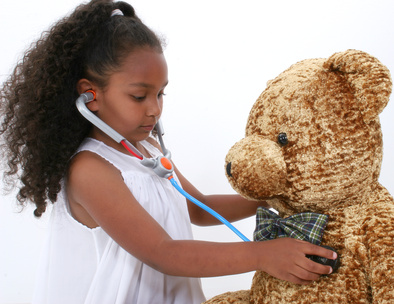 Adorable young girl giving large bear a health check up with toy stethoscope. Shot in studio over white.